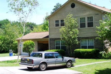 yellow traditional duplex with car in driveway