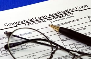 commercial loan application with a pen and glasses